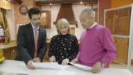 MS mature couple and salesman standing in display of traditional kitchen furniture discussing plans
