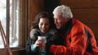 mature couple drinking coffee and talking and laughing in the lodge of a ski resort