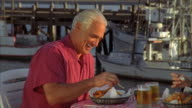 CU, PAN, Mature couple eating fish and chips in harbor, Morro Bay, California, USA,