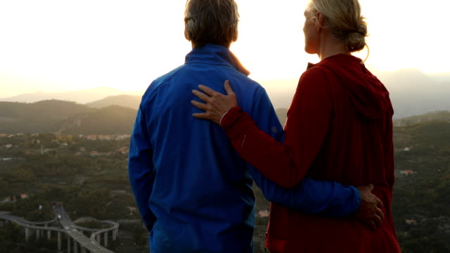 Mature couple explore rocky crest overlooking hills, valley