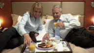 MS, Mature couple having breakfast on hotel bed, Montreal, Quebec, Canada
