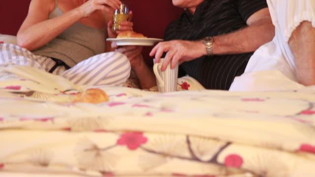 Mature couple in bed having breakfast