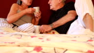 Mature couple in bed talking and drinking coffee