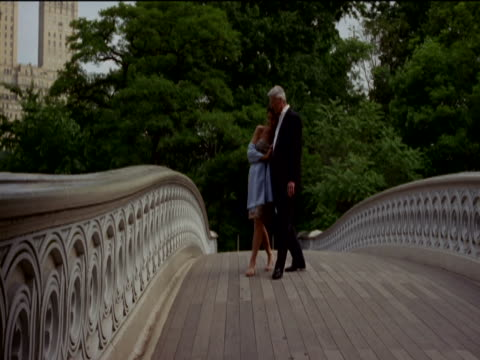 Mature Couple in Evening Dress Walk Side by Side Over a Stone Bridge in Central Park, New York