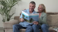 Mature couple looking at brochure and thinking about their vacation