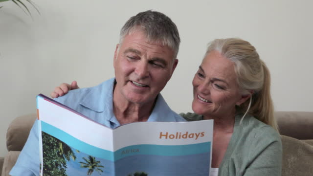 Mature couple looking at holiday brochure