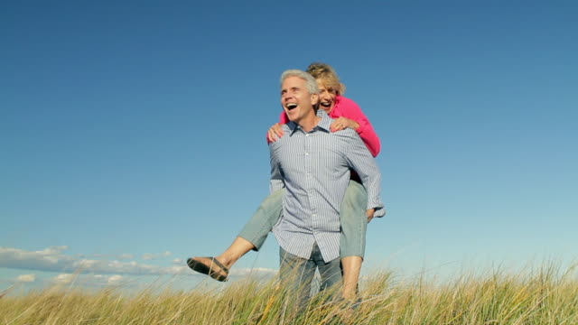 WS Mature couple piggy back ride in beach grass / Sea Bright, New Jersey, USA
