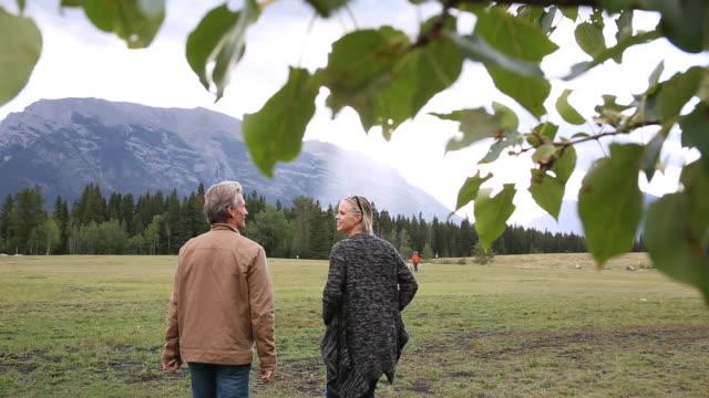 Mature couple walk into mountain meadow, take pic