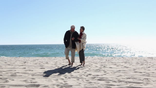 Mature couple walking arm in arm on the beach