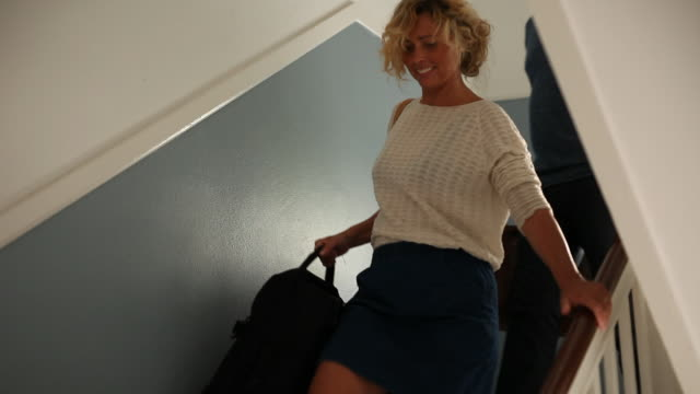 Mature couple walking down staircase with suitcases