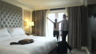 Mature couple walking into a hotel room and hugging