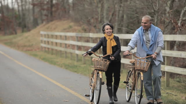 Mature couple walking with bicycles