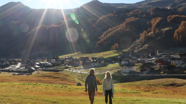 Mature couple walks across mountain meadow, look out over village