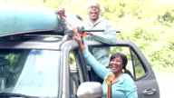 Mature couple with canoe tied to roof of car