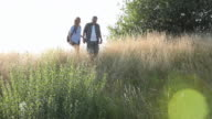 Mature couple with rucksacks hiking in long grass