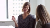 MS Mature female businesswoman in discussion with female colleague at conference table in office