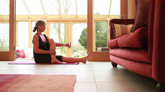 Ältere Frau Ausübung yoga wie zu Hause fühlen.