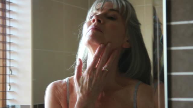 Mature female in bathroom applying crème