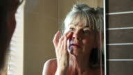 Mature female in bathroom, applying eye cream