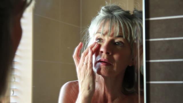 Mature female in bathroom, applying eye cream