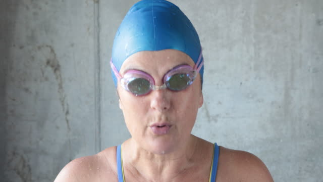 Mature female swimmer lifts head up and takes goggles off smiling