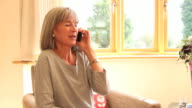 Mature female talking on phone at home