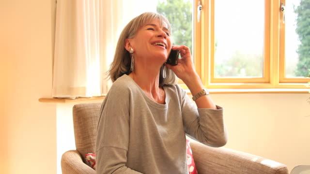 Reife Frau reden am Telefon zu Hause