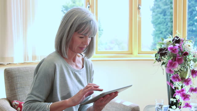 Mature female with computer tablet at home
