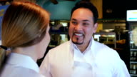 Mature Hispanic chef in Tex-Mex restaurant, training waitress in kitchen