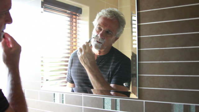 Mature male shaving and looking in mirror