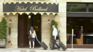 Mature man and a woman entering a hotel with their suitcases