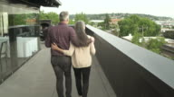 Mature man and a woman walking arm in arm on a rooftop terrace