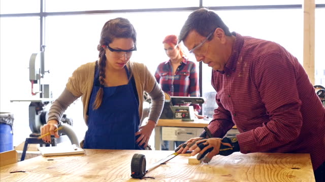 Mature man and young woman work together measuring wood in community workshop