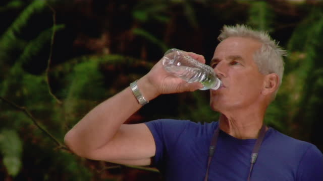 Mature man drinking bottled water while birdwatching in forest