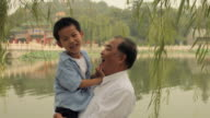 MS Mature man embracing his grandson by lake / China