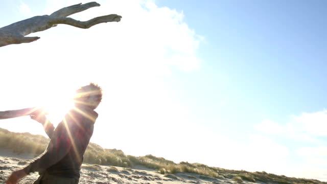 Mature man exercises on shoreline driftwood