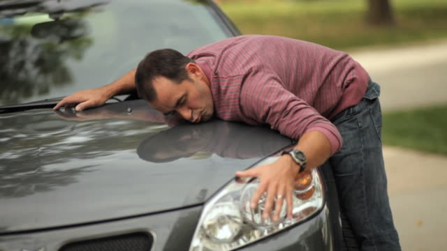 MS Mature man hugging his car / Neenah, Wisconsin, USA