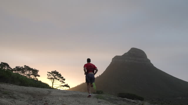 Mature man jogging in hills above city