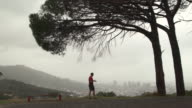 Mature man jogging in hills above city