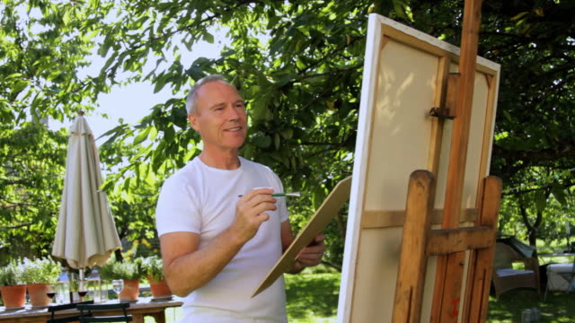 MS Mature man painting in garden / London, United Kingdom