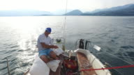 Mature man sailing on a lake.