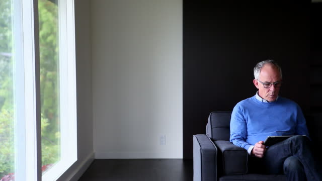 MS Mature man sitting on couch in contemporary home looking out window and looking at digital tablet/Seattle, Washington, USA