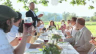 MS Mature man standing up giving toast with friends and family at banquet table outside/Washington, USA