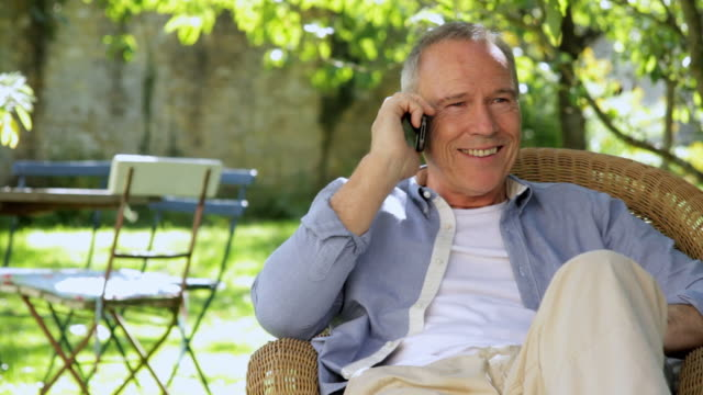 MS Mature man talking on phone in garden / London, United Kingdom