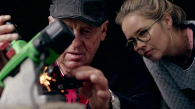 Reifer Mann lehrt wie man Kettensäge Spitzer. Arbeiten mit Tochter