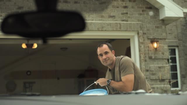 MS Mature man throwing bucketful of water on windscreen of car / Neenah, Wisconsin, USA