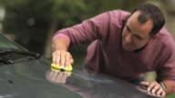 MS Mature man waxing and polishing car / Neenah, Wisconsin, USA