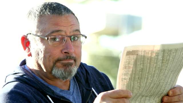 Mature man wearing eyeglasses reads newspaper
