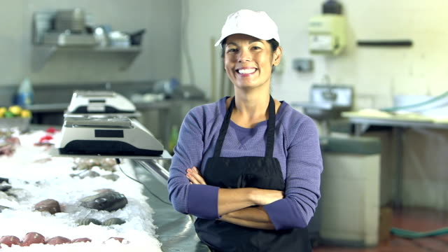 Mature mixed race woman working in fish market