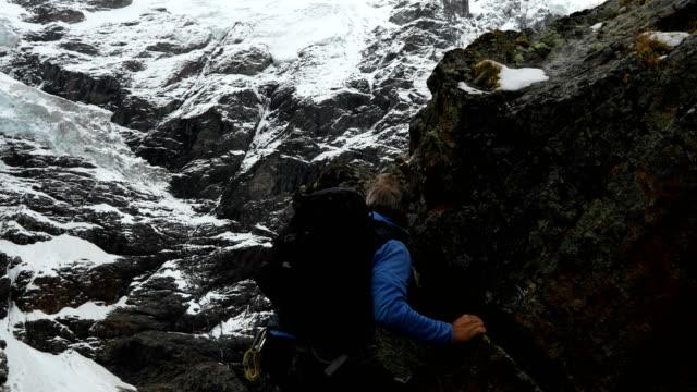 Mature mountaineer ascends peak beneath a glaciated mountain face